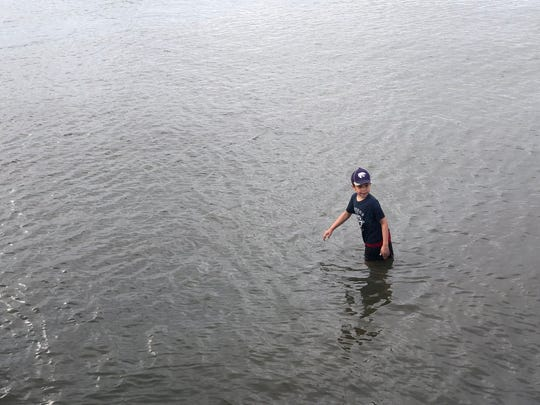 Noah Fortin, 8, who is at his first Pony Swim, decided to escape the crowd as he and others prepare to watch the Chincoteague event from the water Wednesday morning.