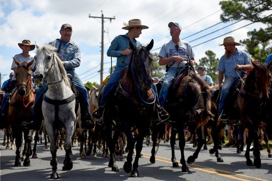 Led by the Saltwater Cowboys, the parade following the Pony Swim on Chincoteague Island, Virginia, kicks off on July 24, 2019.