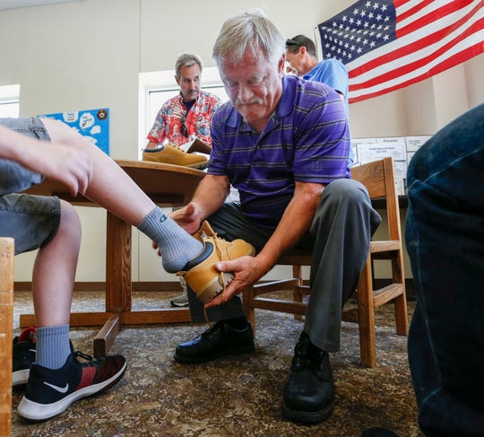 Kiwanis Club member Bill Cox, fits a pair of work boots on a resident of the Good Samaritan Boys Ranch on Wednesday, July 24, 2019. The Kiwanis Club donated more than 80 pairs of boots to boys on the ranch.