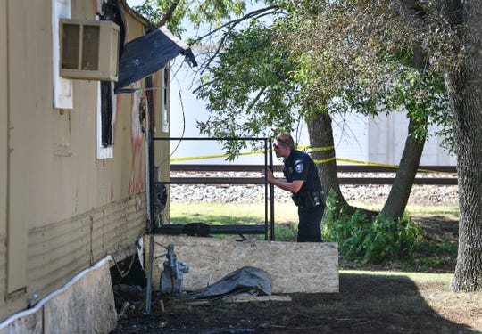 Investigators examine the scene of a fire at a mobile home at 420 Minnie Street Wednesday, July 24, 2019, 420 in Paynesville.
