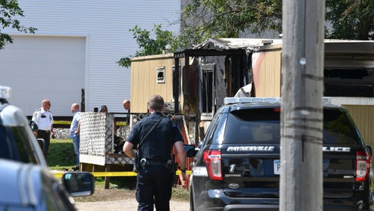 Investigators and officers gather near the the fire scene at 420 Minnie Street Wednesday, July 24, 2019, 420 in Paynesville.