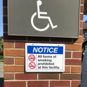 A notice is posted outside a main entrance that states the new no-smoking policy at the St. Cloud VA Health Care System.