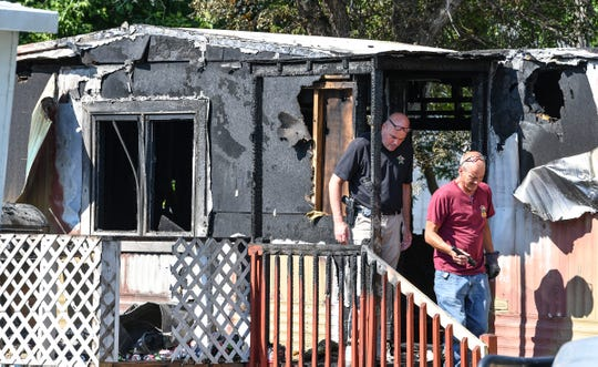 Investigators walk through the entryway to a mobile home while investigating the scene of a fire at 420 Minnie Street Wednesday, July 24, 2019, 420 in Paynesville.
