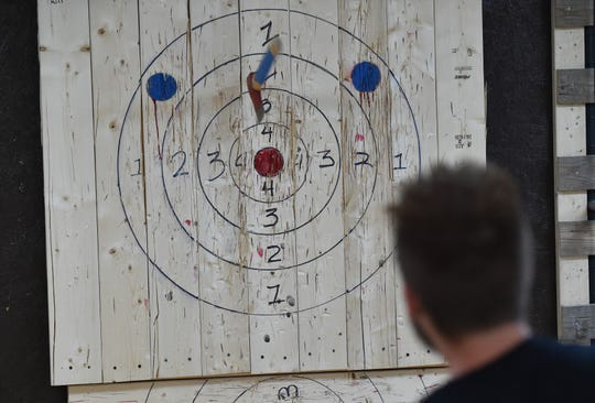 Axe Em, an indoor axe throwing venue in Port St. Lucie. Games are played and scored similar to darts, with axes thrown against pine wood targets.