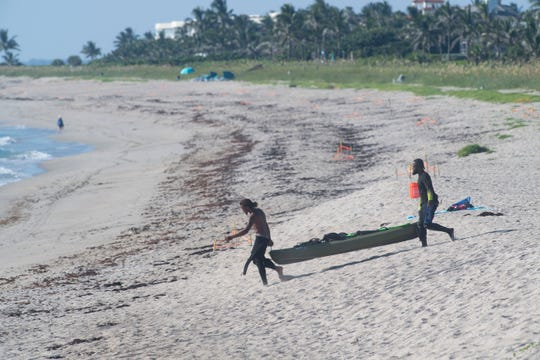 Dimitri Faulkner (left), of Georgia, and Curtis Johnson, of Fort Pierce, walk a kayak to the ocean during the 48 hour lobster mini-season Wednesday, July 24, 2019, at Bathtub Reef Beach in Martin County.
