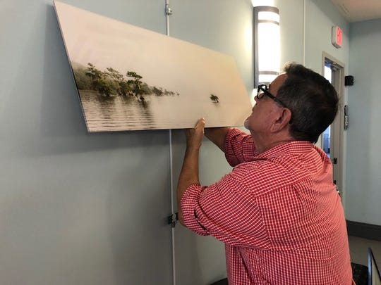 Mark Wygonick hangs a photograph created by Phil Reid Photography in Vero Beach.