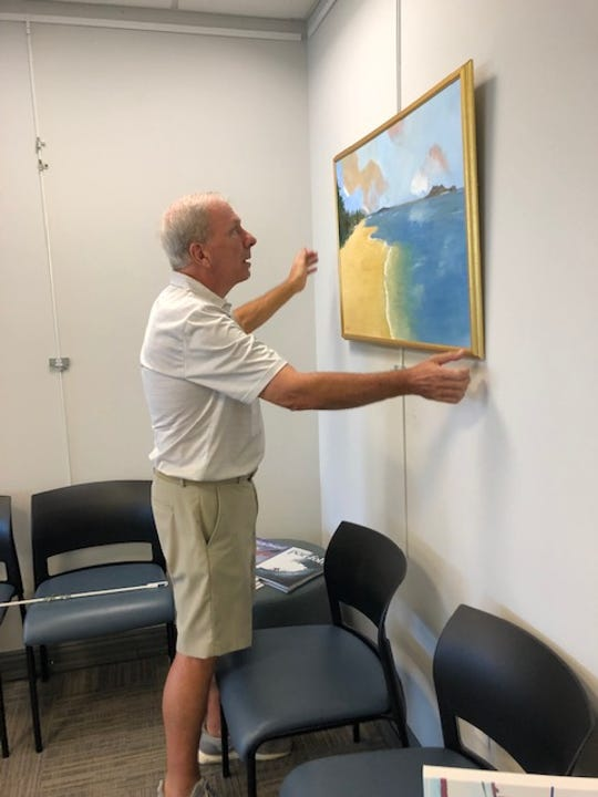 Artist Peter Polk adjusts the height of one of his paintings that hangs in the passenger departure lounge at Vero Beach Regional Airport.