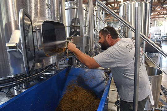 Mike Malone, co-founder of  Walking Tree Brewery, cleans up the mash from a tank in the first phase of creating a batch of craft beer at the brewery on Monday, July 15, 2019, in Vero Beach.