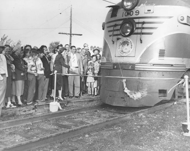 Trucy Kromhout cut the ribbon and June Zigrang christened the New Royal Palm train in front of a crowd of 1,000 people Dec. 23, 1949, in Vero Beach. Standing in front the the locomotive (left to right) are Executive Secretary of the Chamber of Commerce E.G. Thatcher, City Councilman Lou Burger, Zigrang, FEC Railroad Special Representative Hamilton, Kromhout, and Manager of the Florida Theatre and Chairman of the reception Committee Archie Adams.