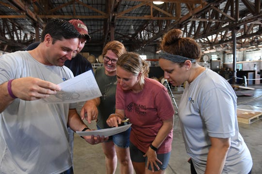 Adam Neal (from left), Patrick Dove, Brooke Malone, Laurie Blandford and Lindsey Leake view the design for the labels of the Indian River Press Journal beers for the Vero Beach Centennial on Monday, July 15, 2019, at the Walking Tree Brewery in Vero Beach.