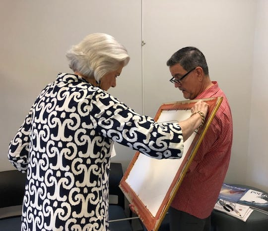 Barbara Hoffman, executive director of the Cultural Council of Indian River County,  helps artist Mark Wygonick adjust the hanging system on the back of a painting on display at Vero Beach Regional Airport.