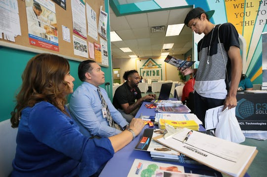 Sebastian Jimenez, 19, talks with Rachel Soto, left, Jorge Cataneda and Michael Thompson from Workforce Solution Borderplex at a job fair at the P.R.I.D.E. Center Wednesday. The Preparation and Resources for Independence through Determination with Excellence (PRIDE) Center offers assistance to current and former youth in foster care helping them work toward self-sufficiency.