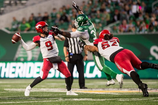 Calgary Stampeders quarterback Nick Arbuckle (9) attempts to throw the ball under pressure from Saskatchewan Roughriders defensive lineman Charleston Hughes (39) during the first half of a Canadian Football League game in Regina, Saskatchewan July 6.