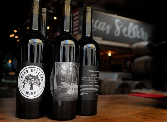 "Bottles of wine are seen in the doorway between Lucas Sellers Wine and the Enegren Brewing Co. biergarten in Moorpark. The winery's cabernet sauvignon, center, includes a 1944 photograph of late family member Chloedelle (""Chloe"") Sellers on the label."