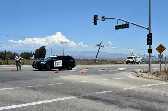 A utility pole hangs at the intersection of Pleasant Valley and Dodge roads on the Oxnard Plain on Thursday as Highway Patrol officers temporarily detoured traffic around the intersection.