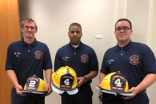 Vineland Fire Department volunteers, (left-to-right) Howard Ore, Luis Martinez-Pena, and Anthony Lopez traded in their recruit helmets for those that correspond with the station where they now serve.