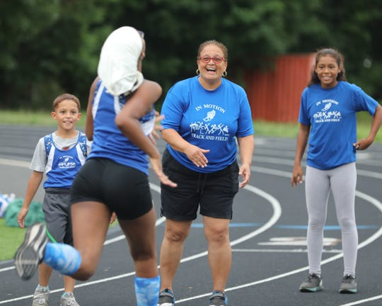 Deborah Thomas cheers on her team during practice at Spring Valley High School July 22, 2019. Thomas, a widow with 4 kids, adopted 5 kids and  started a track with them in mind. It has Junior Olympic winners and collegiate athletes.