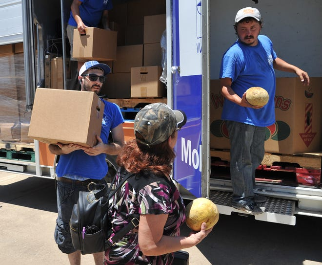 In this file photo, Wichita Falls Area Food Bank Mobile Pantry driver, Mason Sparks, left, and volunteer Justin Black help distribute food from the food bank's mobile pantry. The food bank announced their mobile pantry schedule for July.