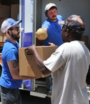 Wichita Falls Area Food Bank Mobile Pantry driver, Mason Sparks, left, and volunteer Justin Black help distribute food from the food bank's mobile pantry Wednesday afternoon.