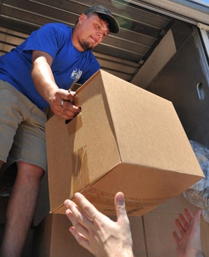 Wichita Falls Area Food Bank Mobile Pantry driver, Vincent Reed hands out healthy food boxes, Wednesday afternoon, during mobile pantry's stop at the Ben Donnell Housing Center located on E. Wichita Street.