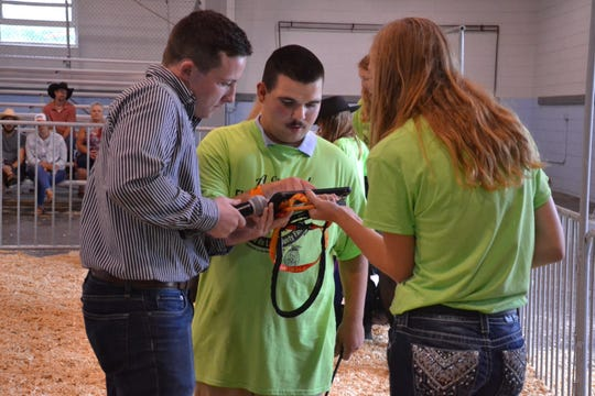 Seth Zimmerman (center) uses his iPad to communicate with judge Alex Costello in the show ring.