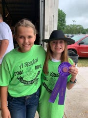 Ava Zelazoski (right) is joined by mentor Klair Grinstead as she proudly shows off her blue ribbon.