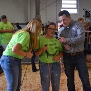 Special exhibitor Olivia Schrader (center) is joined by her mentor Katie Schwanke (left) as she tells judge Alex Costello about her pig.