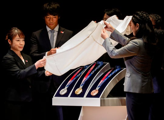 Olympic medalists unveil the Tokyo Olympics medals (L-R; Silver, Gold and Bronze) during the One Year to Go Ceremony at Tokyo Forum in Tokyo, Japan, 24 July 2019.
