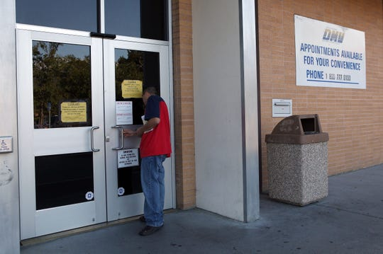 In this 2009 photo, a California Department of Motor Vehicles customer peers into the door of the closed DMV branch in Corte Madera, Calif. The DMV received $240 million in the most recent budget to try and deal with its host of problems.
