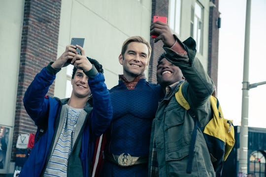 """A grinning Homelander (Anthony Starr) snaps selfies with two young fans after saving their lives in the season premiere of Amazon's """"The Boys."""""""