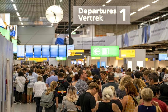 People wait in the departure hall of the Amsterdam-Schiphol airport, southwest of Amsterdam, as a problem with refuelling grounded several dozen planes and hundreds of passengers on July 24, 2019.