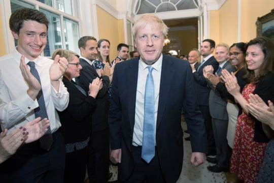 Prime Minister Boris Johnson is clapped into 10 Downing Street on July 24, 2019, by staff after seeing Queen Elizabeth II and accepting her invitation to become prime minister and form a new government.