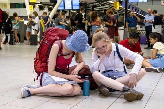People sit on the floor while waiting in the departure hall of the Amsterdam-Schiphol airport, southwest of Amsterdam, as a problem with refuelling grounded several dozen planes and hundreds of passengers on July 24, 2019.