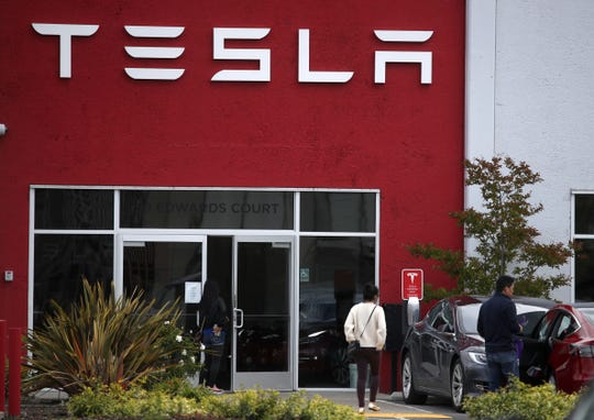 Customers enter a Tesla showroom and service center on May 20, 2019 in Burlingame, California.