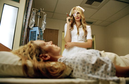 "Elle Driver (Daryl Hannah, top) tries to take out a comatose Bride (Uma Thurman) in ""Kill Bill: Volume 1."""