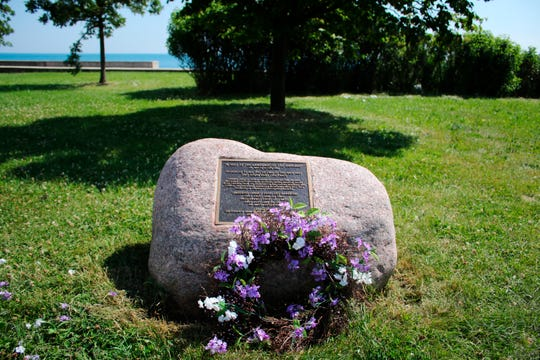 In this July 10, 2019, photo, a wreathe lies in front of a site commemorating the 1919 race riots in Chicago. The plaque is near the area where black teenager Eugene Williams was struck in the head with a rock and drowned in Lake Michigan, sparking race riots.