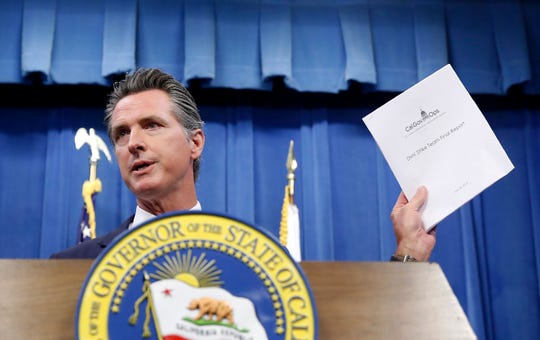 Gov. Gavin Newsom displays a report detailing efforts by the Department of Motor Vehicles to improve customer services during a news conference in Sacramento, California on Tuesday.