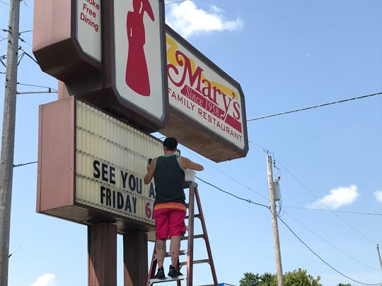 A worker changes the sign on Mary's Family Restaurant on N. Richmond Street in Appleton. It will reopen Friday, six days after a storm cut off its power.