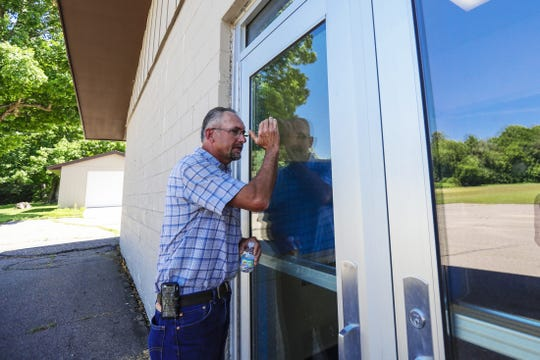 Wade Reimer of Shepherd's Watch takes a peek through a glass door of Mattoon Elementary School July 12. He hopes to operate a Christian community center and choice school at the site, but has gotten caught in the cross-hairs of a legal battle.