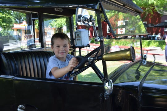 Dominic Smitter of Grand Rapids honks the horn on a 1935 Austin Taxi at the Gilmore Car Museum in Hickory Corners on Wednesday, July 24, 2019.