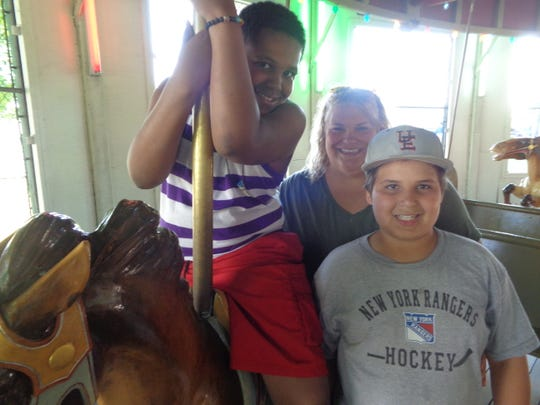 From left, Emil Brown, Jen Broder and Lucas Broder get ready to ride the carousel at West Endicott Park in Endicott. The Broder family has been hosting Emil as a Fresh Air child for seven years.