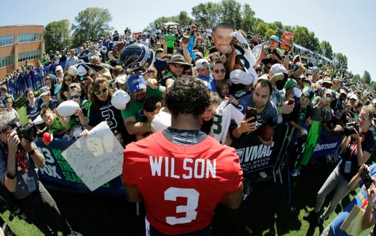 Seattle Seahawks quarterback Russell Wilson (3) signs autographs for fans following NFL football training camp, Thursday, July 25, 2019, in Renton, Wash.
