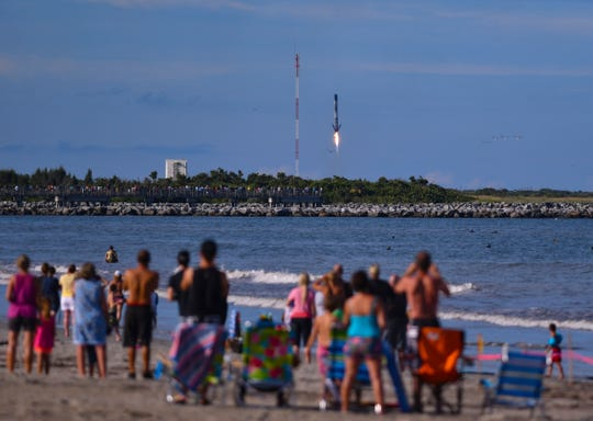 People on the beach at Cherie Down Park in Cape Canaveral watch and photograph the  launch of a Falcon 9 rocket from Cape Canaveral Air Force Station's Launch Complex 40 Thursday evening at 6:01 p.m. on a resupply mission to the International Space Station and the successful landing of the booster back at Landing Zone 1 at CCAFS.