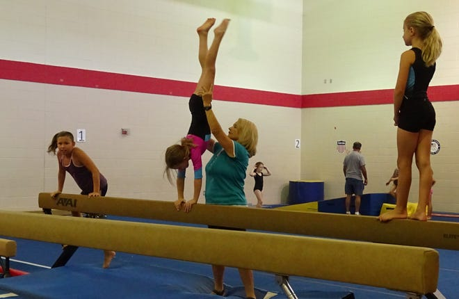 Rhonda Miller, center, works with Molly Perkins on the balance beam during a pre-team gymnastics class on Tuesday at the Bucyrus Area YMCA. At left, Ryleigh Foust climbs onto the beam while Olivia Moore, right, waits her turn.