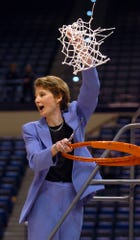 Boston College head women's basketball coach Cathy Inglese holds up the net after she cut the last strands after Boston College won the Big East Championship tournament by defeating Rutgers 75-57 in Hartford, Conn., Tuesday, March 9, 2004.  Inglese died on July 24, 2019 as the result of a traumatic brain injury suffered in a fall.