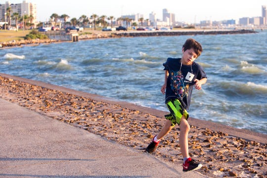 John Butanda, 10, participates in a running club on Thursday, July 25, 2019, at Cole Park. Kids from any school, and their parents, are encouraged to participate in the program.