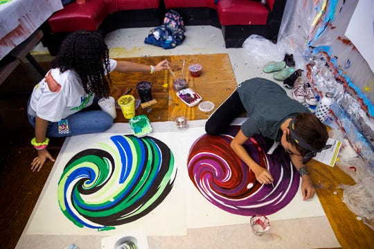 Heaven Garrison, left, 13, and Kenzley Dowell, 13, paint a fabric piece to be installed on the side of K Space Contemporary on July 22, 2019.