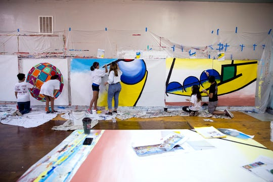 Students paint fabric pieces to be installed on the side of K Space Contemporary on July 22, 2019.