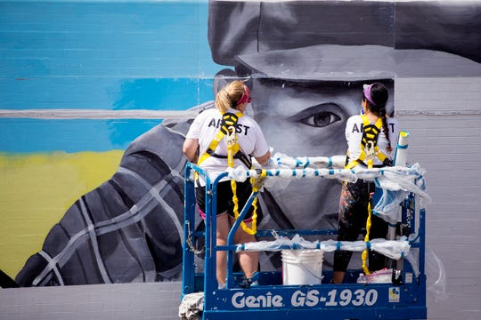 Lori Edwards, left, and Sandra Gonzalez install a mural on the side of K Space Contemporary on July 16, 2019.
