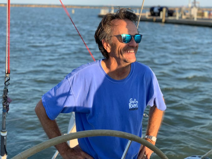 Captain Steve Hastings smiles at other crew members aboard his sail boat Passion on Wednesday, July 24, 2019.